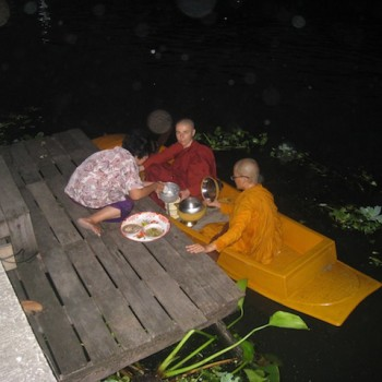 Woman offering alms in front of her house by the canal